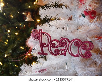 The word PEACE spelled out in pink glittered lettering is an ornament hanging on a white Christmas tree with glowing lighted evergreens in the background.