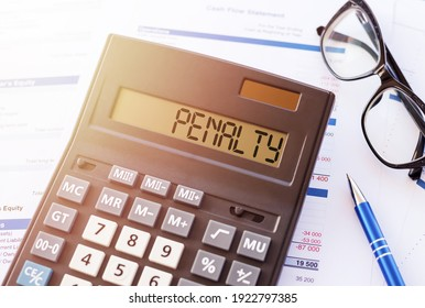 Word PENALTY on the display of a calculator on financial documents.
