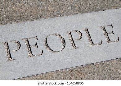 The word people stenciled in concrete.