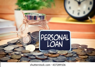 Word Personal Loan on mini chalkboard and coin in the jar with blurred background of books, green plant and clock. Financial Concept.