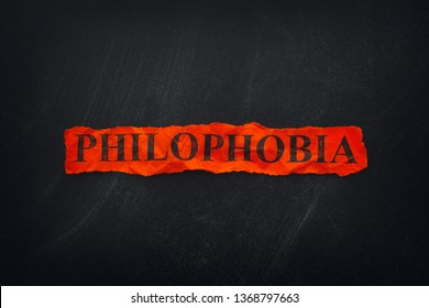 Word Philophobia on red torn piece of paper. Philophobia is the fear of love. Close up.