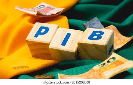 The word PIB ( gross domestic product ) written on wooden cubes with some Brazilian Real banknotes and coins on yellow and green fabrics, making reference to Brazil. Brazilian Portuguese language.