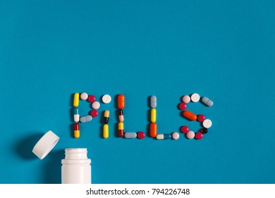 Word Pills With Colored Pills And Tablets On A Blue Background. Creativity Medicine Concept