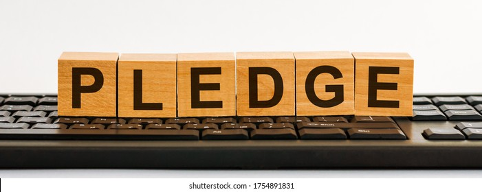the word of PLEDGE on building blocks concept, black keyboard background.