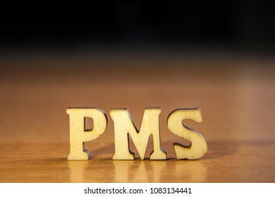 The word 'pms' made of wooden letters. wood inscription on table and dark black background