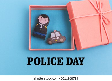 The word Police Day and the gift box inside there are wooden blocks in the shape of police officers and patrol cars. Suitable for education and appreciation in the form of cards, banners and posters.