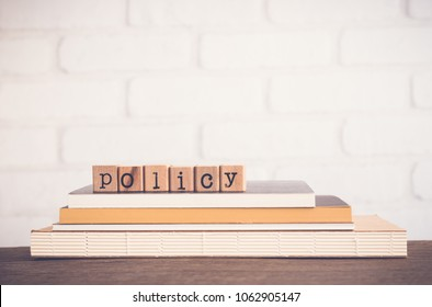 The word Policy, alphabet on wooden rubber stamps on top of books and table. Bricks background, blank copy space, vintage minimal style. Business privacy legal documents, advice information concepts.