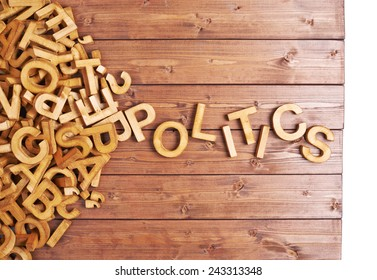 Word politics made with block wooden letters next to a pile of other letters over the wooden board surface composition