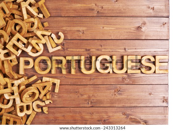 Word portuguese made with block wooden letters next to a pile of other letters over the wooden board surface composition