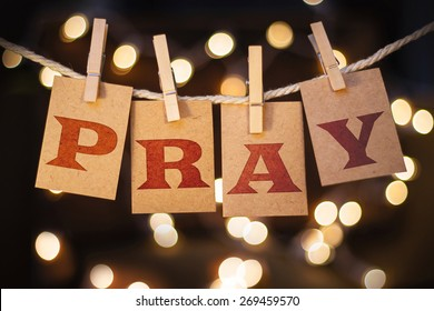 The word PRAY spelled out on clothespin clipped cards in front of glowing lights.