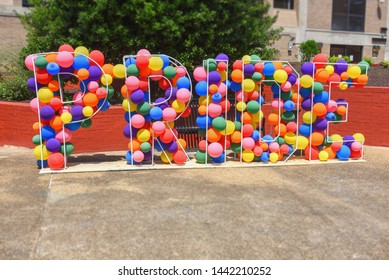"""The word """"PRIDE"""" spelled out in rainbow balloons in a life-size display stand on a sidewalk. A colorful celebration of LGBT Pride."""