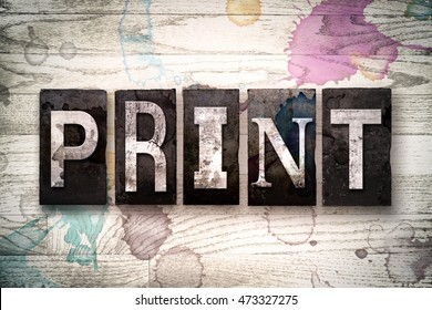 """The word """"PRINT"""" written in vintage dirty metal letterpress type on a whitewashed wooden background with ink and paint stains."""