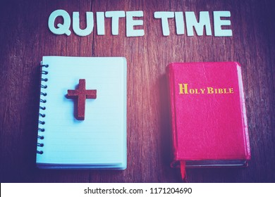 "Word "" Quite Time "" with holy bible and wood cross over small note book on wooden background, Christian concept"