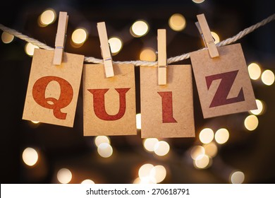 The word QUIZ printed on clothespin clipped cards in front of defocused glowing lights.