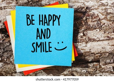 Word quotes of BE HAPPY AND SMILE on colorful memo papers with wooden background.