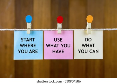 Word quotes of START WHERE YOU ARE, USE WHAT YOU HAVE, DO WHAT YOU CAN on colorful sticky papers hanging by a rope against blurred wooden background.