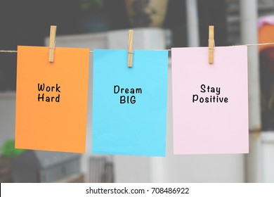 Word quotes of Work Hard, Dream Big, Stay Positive on sticky color papers hanging on rope against blurred background.
