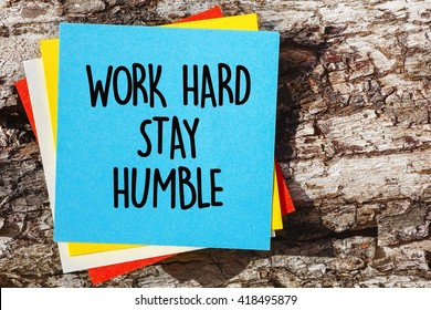 Word quotes of WORK HARD STAY HUMBLE on colorful memo papers with wooden background.