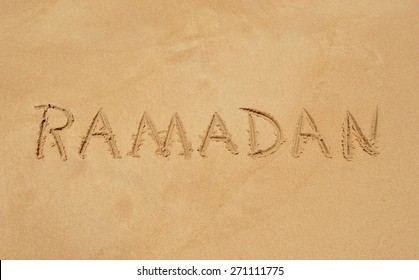 The word  'RAMADAN' written in the sand at a tropical beach