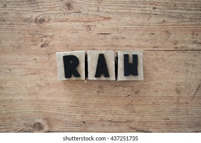 Word raw wrote in raw cardboard alphabet stamp in wood background. Rustic alphabet stamp with black letters.