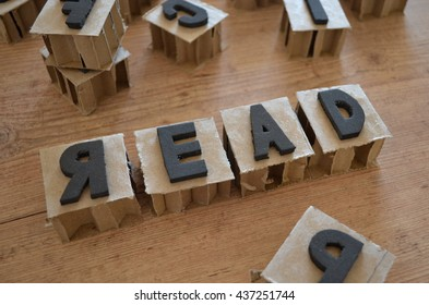 Word read wrote in raw cardboard alphabet stamp in wood background. Rustic alphabet stamp with black letters.