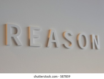 """The word """"reason"""" embossed on a white wall, partially blurred"""
