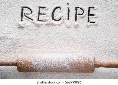 Word recipe in the white flour on the table. Healthy eating and lifestyle.