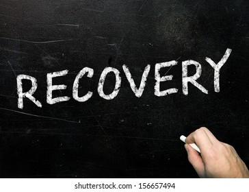 word recovery handwritten with white chalk on blackboard