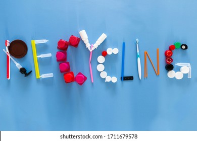 The word recycling composed with various plastic garbage items on colorful background
