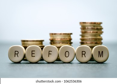 The word REFORM on letter blocks and stand coins, Tax Reform concept.