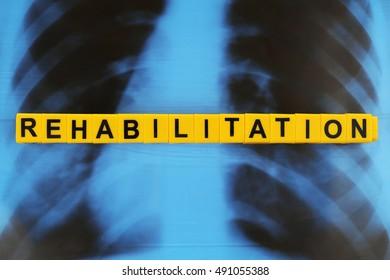 Word REHABILITATION made of alphabet blocks on X-ray image background