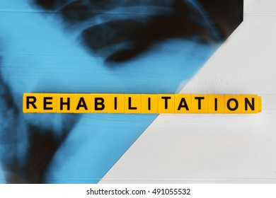 Word REHABILITATION made of alphabet blocks with X-ray image on white wooden background