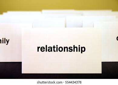 Word Relationship on a white paper card surrounded by other words. Priorities and values concept