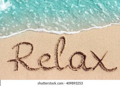 Word Relax handwritten on sandy beach