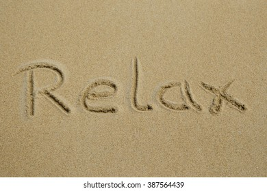 The word relax written in the sand at the beach