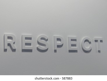 """The word """"respect"""" embossed on a white wall, partially blurred"""