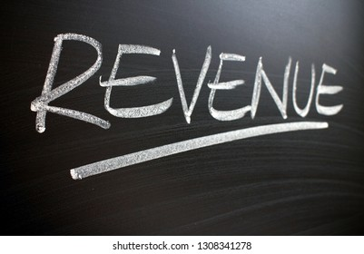 The word Revenue written by hand in white chalk on a blackboard and photographed at an angle