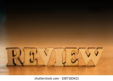 The word 'review' made of wooden letters. wood inscription on table and dark black background