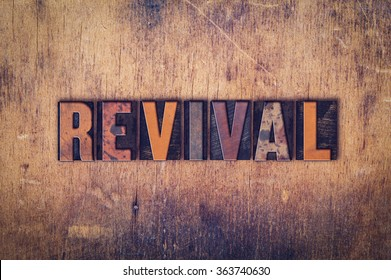 """The word """"Revival"""" written in dirty vintage letterpress type on a aged wooden background."""