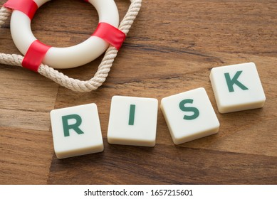 Word RISK and lifebelt on wooden table background. Planning, risk management or insurance and business finance strategy concept.