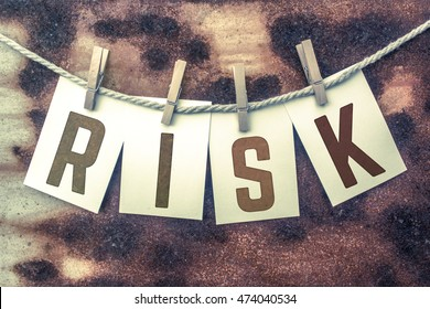 """The word """"RISK"""" stamped on cards and pinned to an old piece of twine over a rusted metal background."""