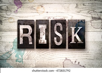 """The word """"RISK"""" written in vintage dirty metal letterpress type on a whitewashed wooden background with ink and paint stains."""
