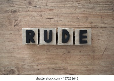 Word rude wrote in raw cardboard alphabet stamp in wood background. Rustic alphabet stamp with black letters.