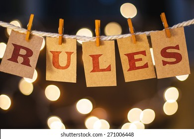 The word RULES printed on clothespin clipped cards in front of defocused glowing lights.