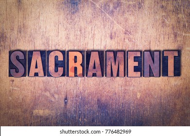 The word Sacrament concept and theme written in vintage wooden letterpress type on a grunge background.