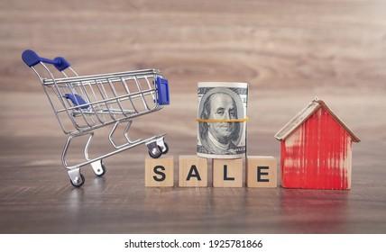 Venta de palabras en cubos de madera con modelo de casa, carro de la compra y dinero.