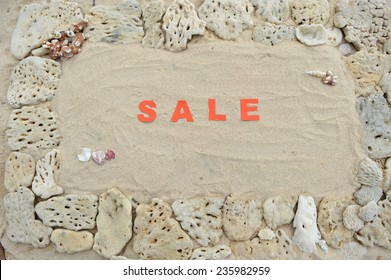 The word 'sale' written with red letters in the sand in a frame of white corals