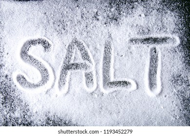 The word salt is written on small crystals of salt scattered on a black table. Background for advertising salt. Table salty. Salted food.