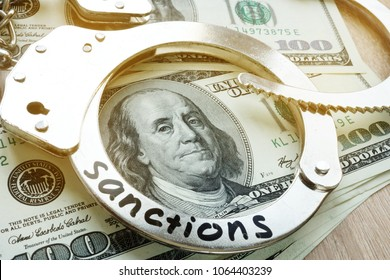 Word sanctions on a handcuffs and American dollar bills. Economical restrictive measures.
