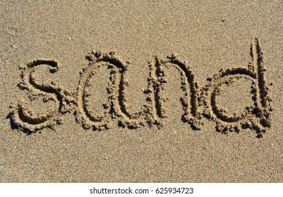 The word sand is written in the sand.